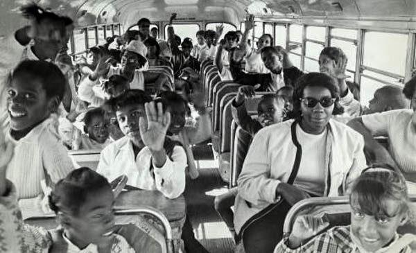 several children waving and schoolteacher on a bus