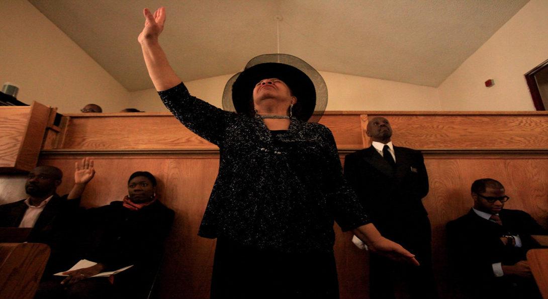 women dressed in black raises her hand in church