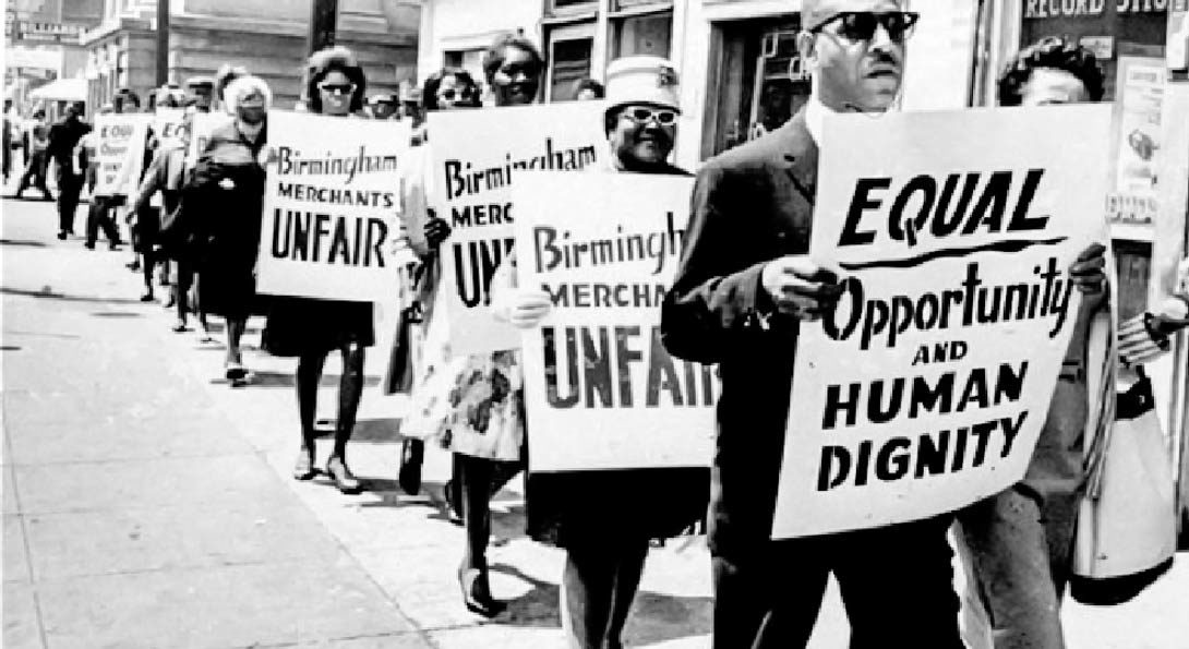 several people marching while holding picket signs