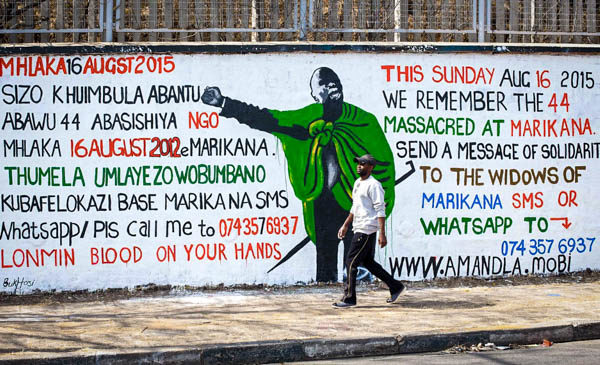 man walking in front of the Marikana mural