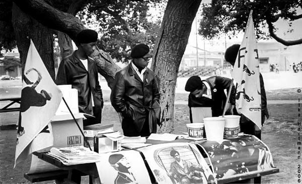 four people in berets and leather jackets standing at a booth table for the Black Panther Party