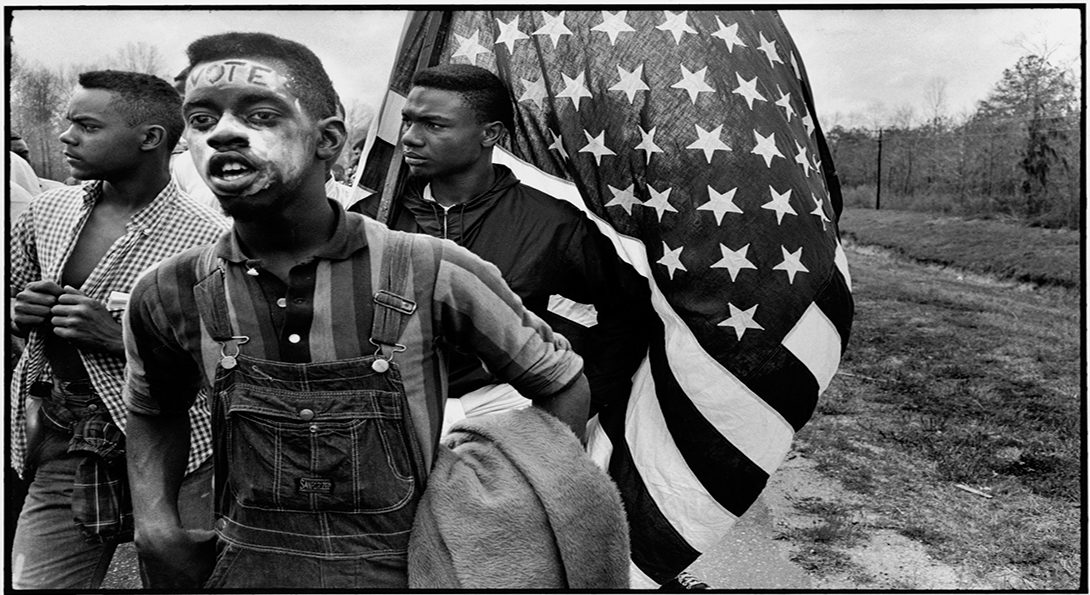 three people marching, one holding an American flag and another with