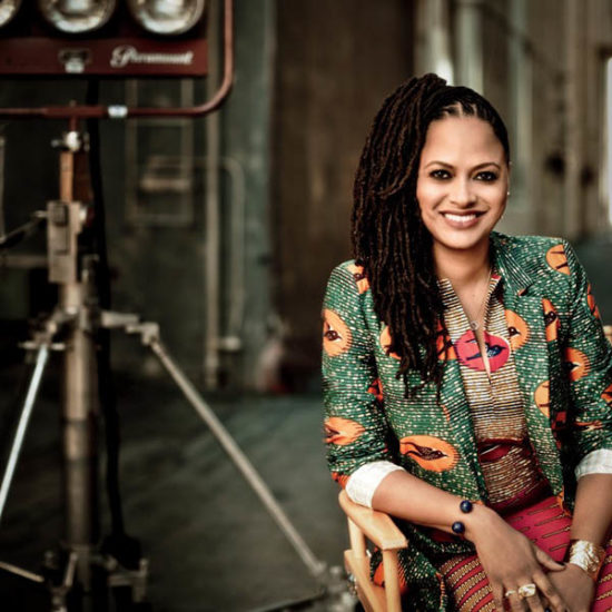 ava duvernay seated in front of movie set lights for photo