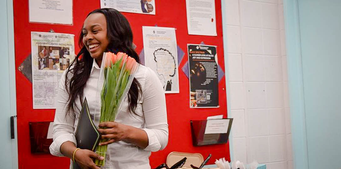 student smiling holding flowers
