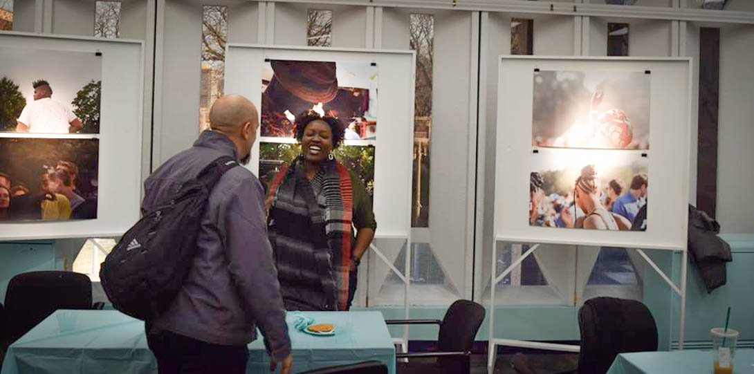 faculty member and alumna speaking in a photo art exhibit