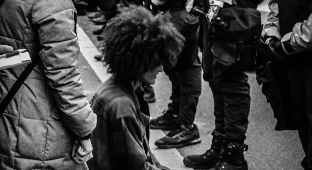person kneeling in front of police in riot gear