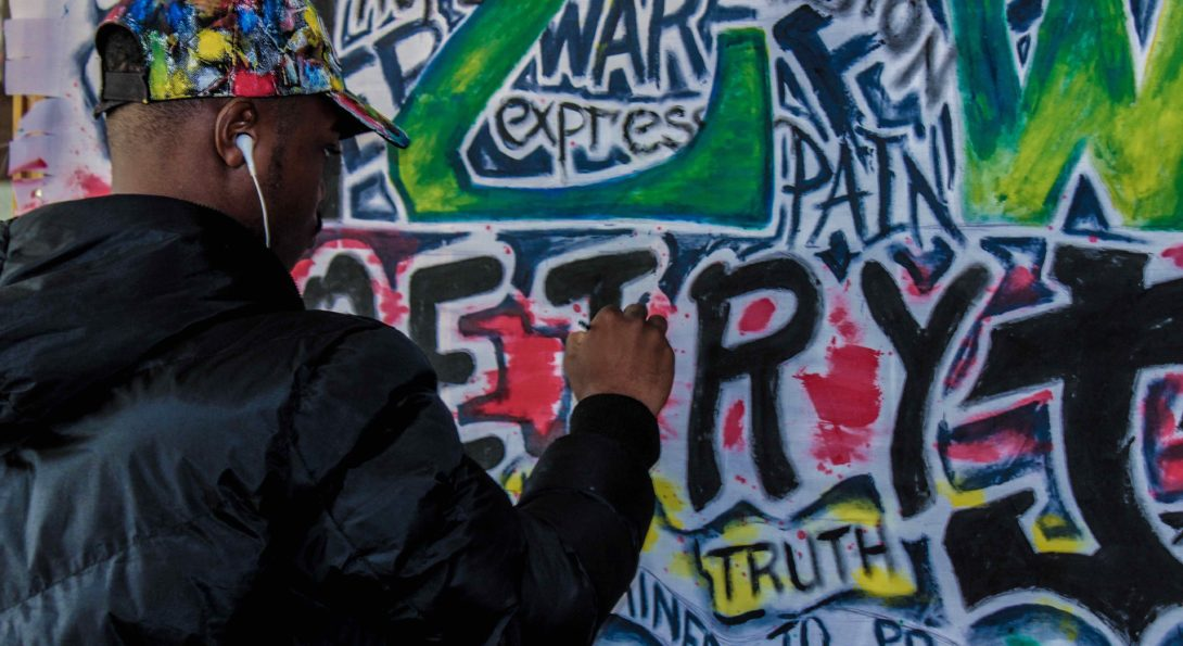 person in hat painting a mural with phrases: