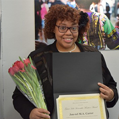 student holding flowers and award