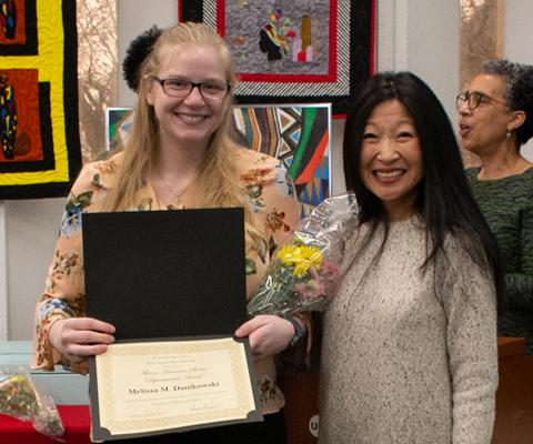 student award recipient posing displaying award