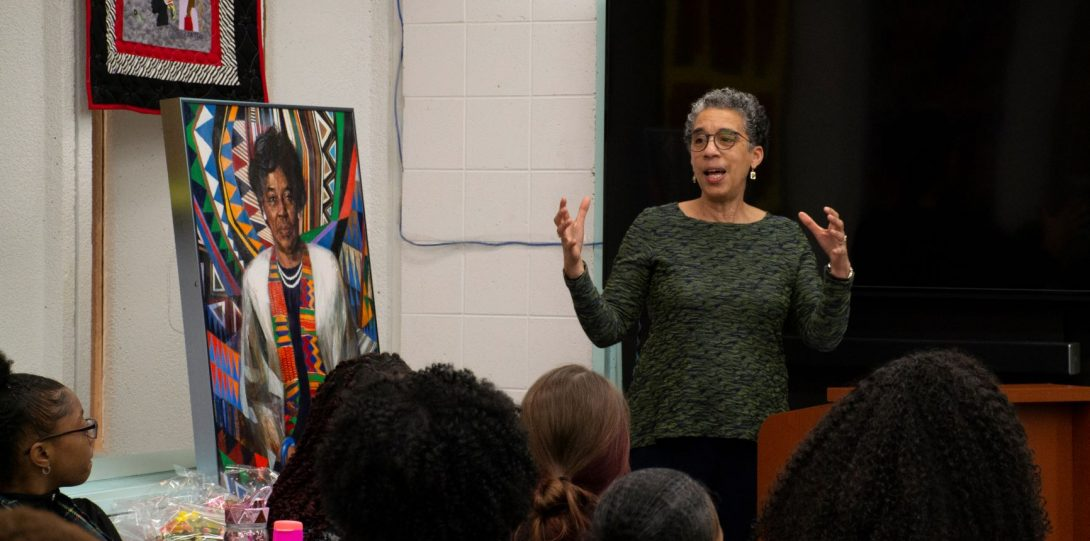 A person stands before a crowd and next to a painting delivers opening remarks to an event