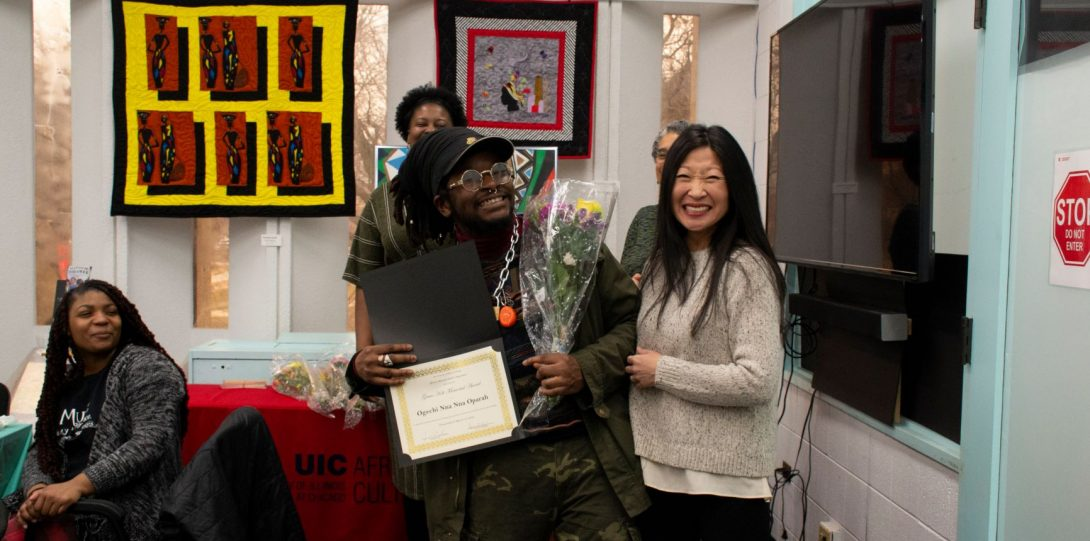 Two people hold flowers and a diploma and pose for a photo together