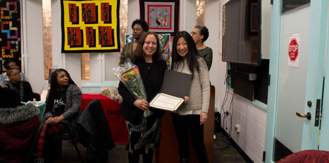 Two smiling people hold flowers and a diploma and pose for a photograph