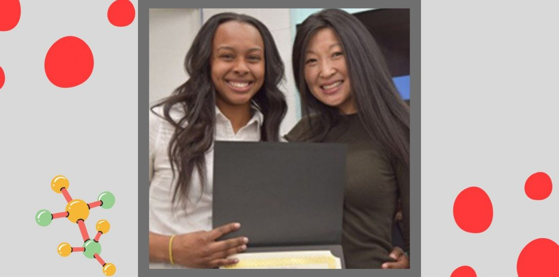 Two people smile and pose for a photo while holding a diploma in their hands