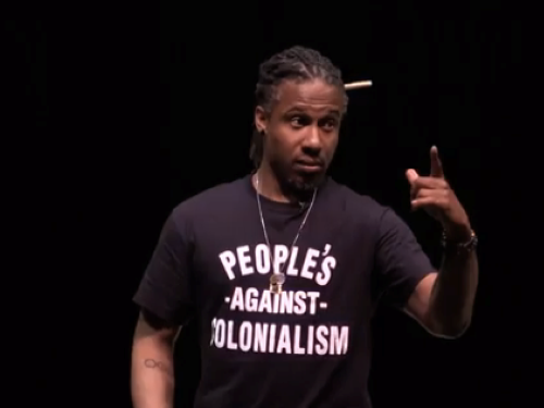 A person in a black shirt that reads Peoples against Colonialism is photographed while speaking in a lecture