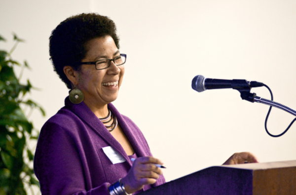A person laughs in front of a microphone and podium