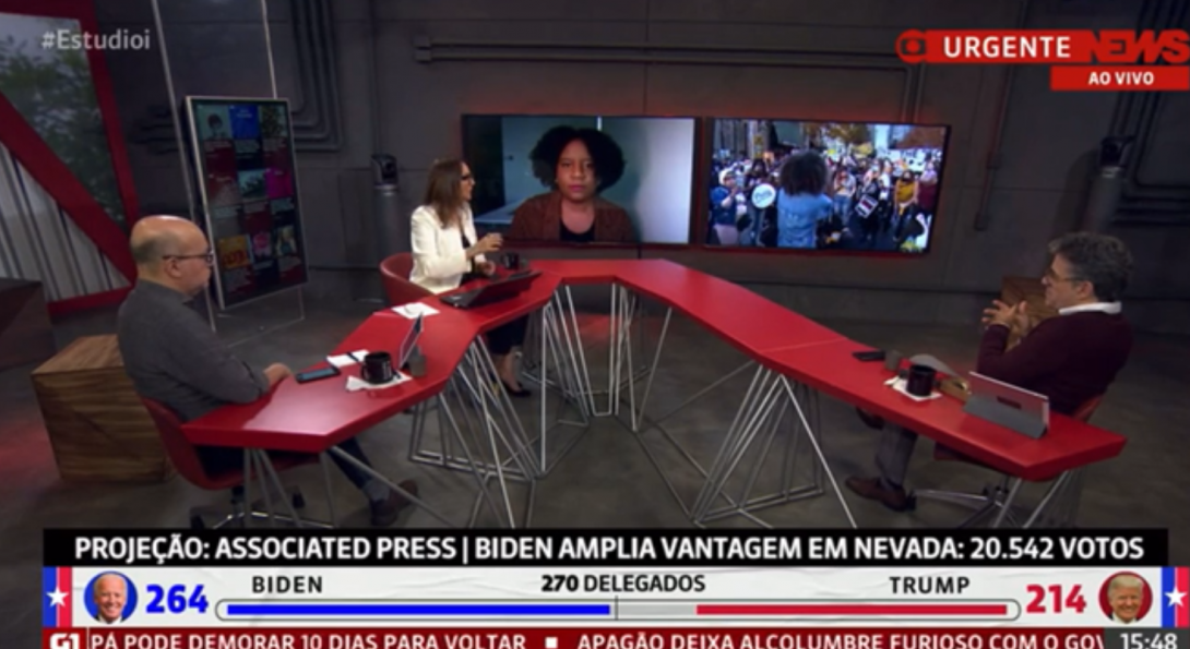 A newsroom with three people interview a person featured on screen