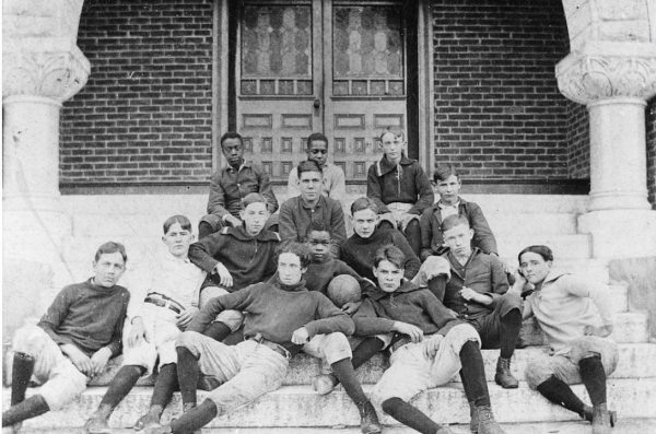 Young football players pose for a photo on the steps of a building entrance