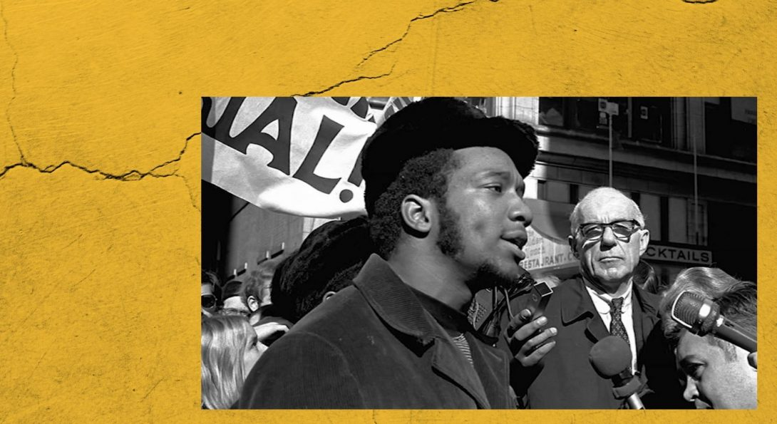 a still of fred hampton surrounded by a crowd and microphones being interviewed