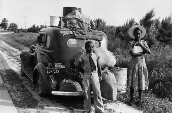 two young people with their luggage strapped to a car stand on a road