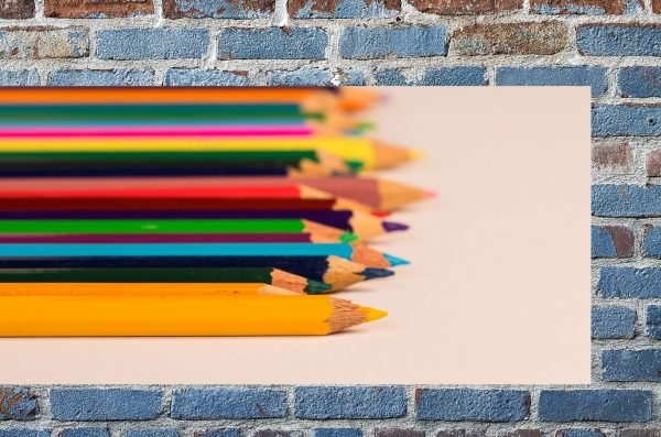 color pencils are superimposed over an image of a blue brick wall