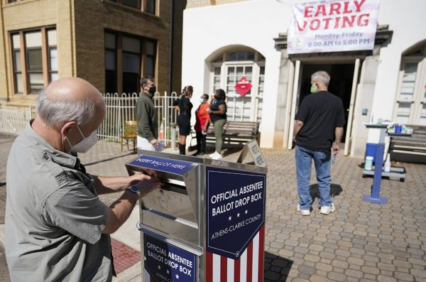 A man drops off a ballot during early voting in Athens, Ga., in October 2020. A new study finds that white boys who grew up with Black neighbors were more likely to register as Democrats 70 years later.