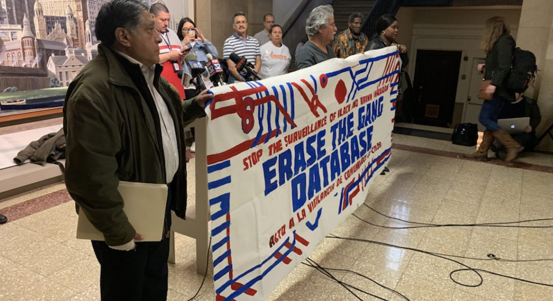 Several people hold banner that reads Erase the Gang Database