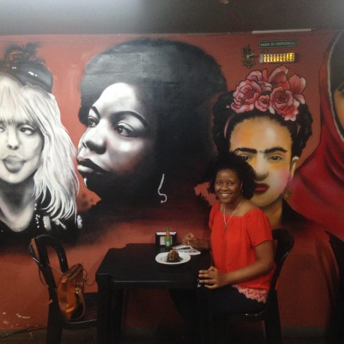 Prof. Harrington sitting at a table in front of a mural of four people
